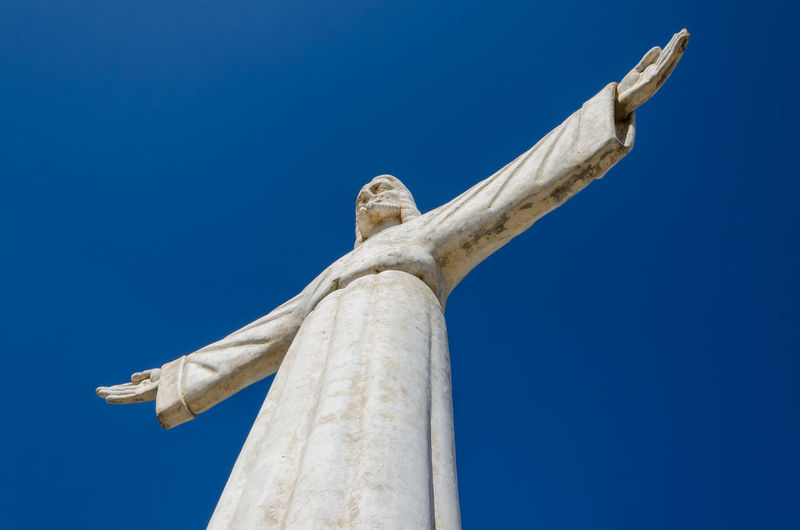 Low Angle View Of Jesus Christ Statue Against Blue Sky, Lubango, Angola