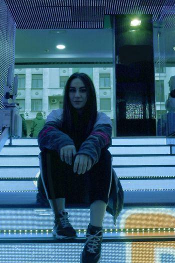 Full length portrait of woman sitting against illuminated building