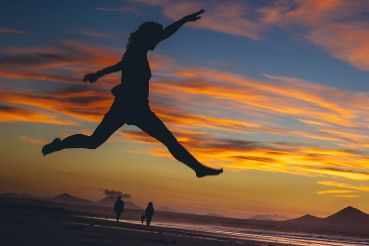 Silhouette people jumping on beach against sky during sunset