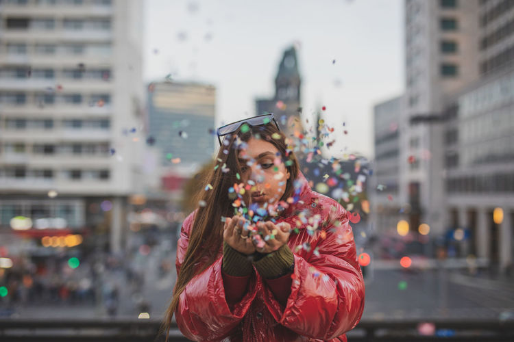 Young Woman Blowing Colorful Confetti In City During Sunset