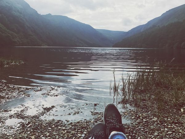 Human Leg Low Section Shoe One Person Mountain Human Body Part Personal Perspective Water Real People Lake Nature Day Standing Lifestyles Outdoors Scenics Winter Beauty In Nature Sky