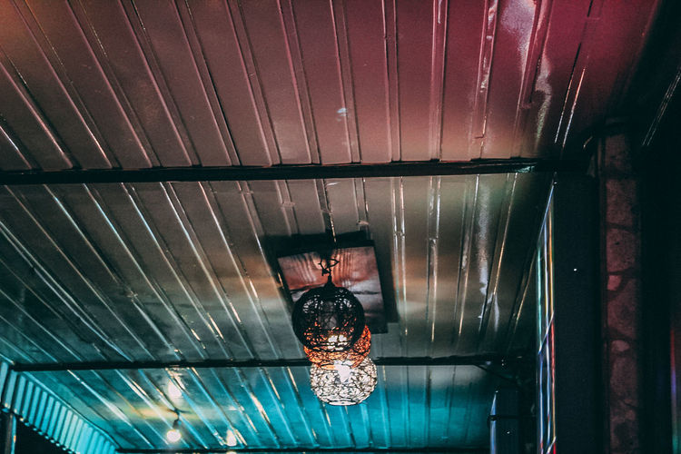 Low angle view of illuminated lights hanging on ceiling at home
