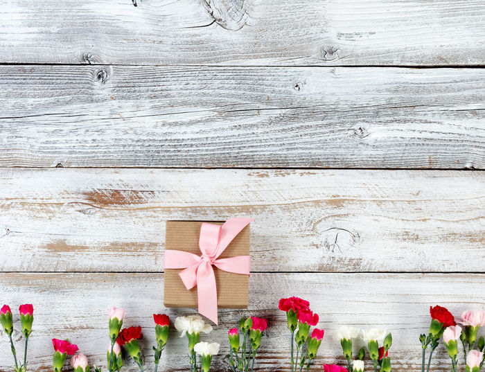 Close-Up Of Pink Flowers And Gift Box On Wooden Table