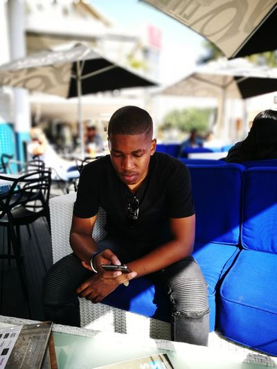 Young Man Using Mobile Phone While Sitting On Sofa At Sidewalk Cafe