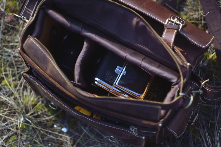 Camera bag Equipment Medium Format Film Camera EyeEm Selects Technology No People Communication High Angle View Close-up Still Life Container Photography Themes Personal Accessory Outdoors Day Grass Leather Black Color