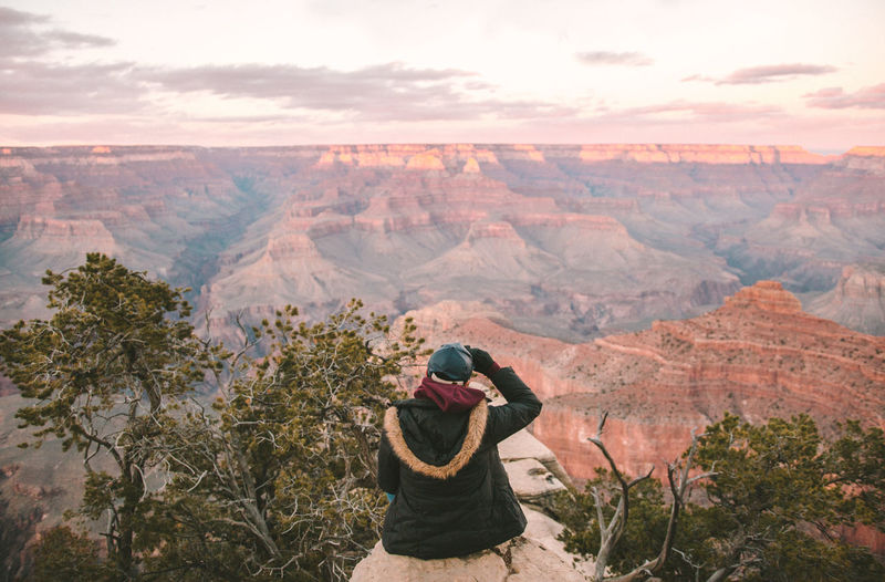 Rear view of person sitting on rock against grand canyon national park