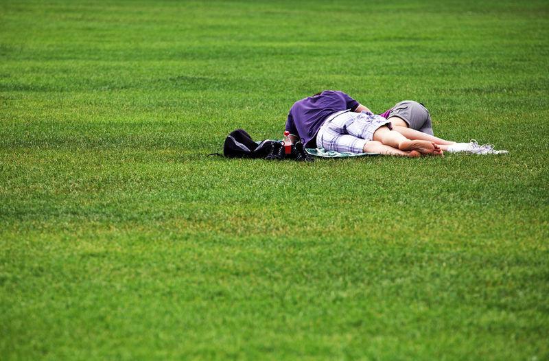 Man and woman sleeping on grassy field