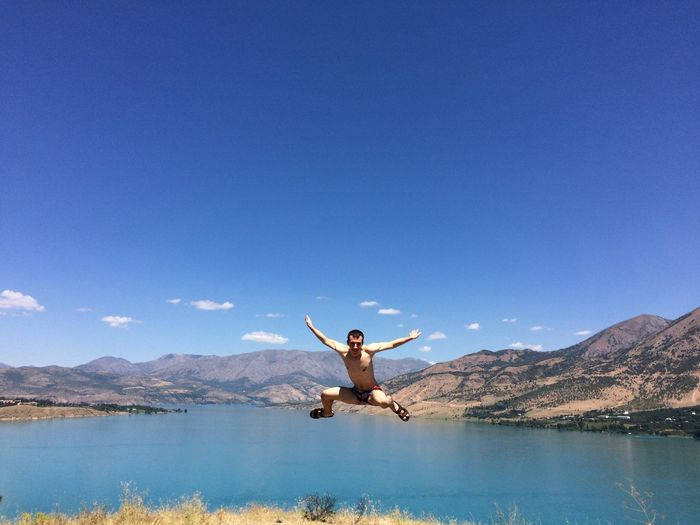 Shirtless man jumping at lake against sky