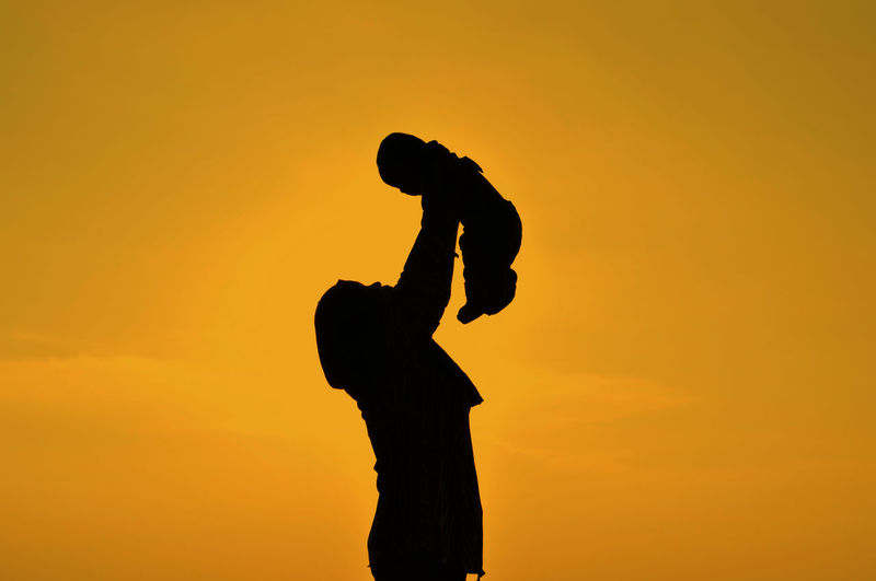 Low angle view of silhouette woman holding aloft baby against orange sky