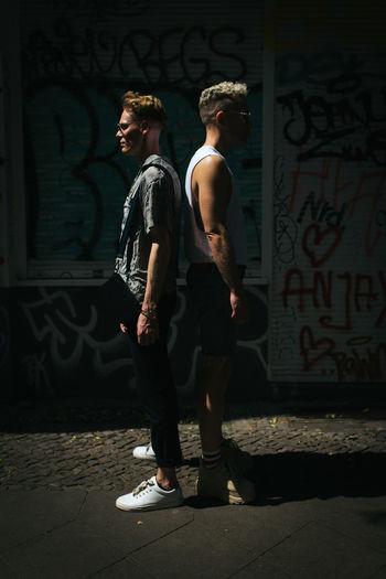Full length of men standing against graffiti wall