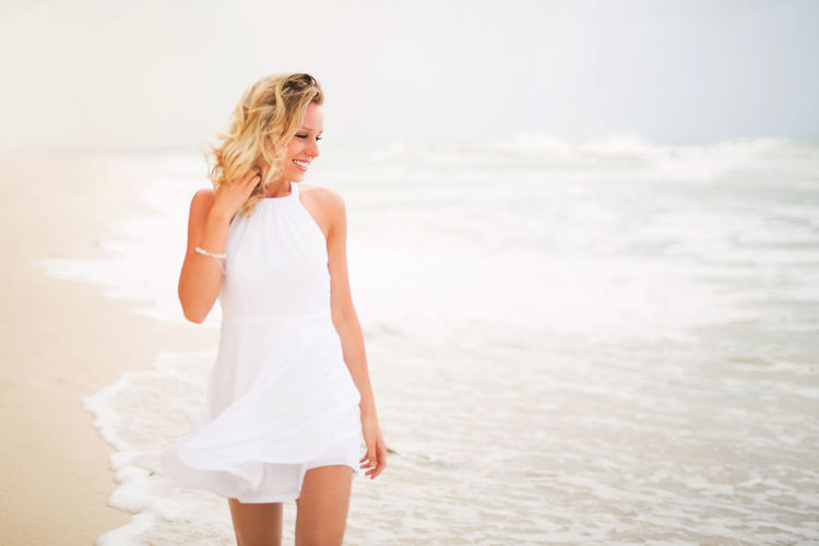 Dress Beach Beautiful Woman Beauty Blond Hair Bride Day Happiness Horizon Over Water Long Hair Nature One Person One Woman Only One Young Woman Only Only Women Outdoors Sand Sky Smiling Summer Vacations Wave Wedding Dress Young Adult Young Women