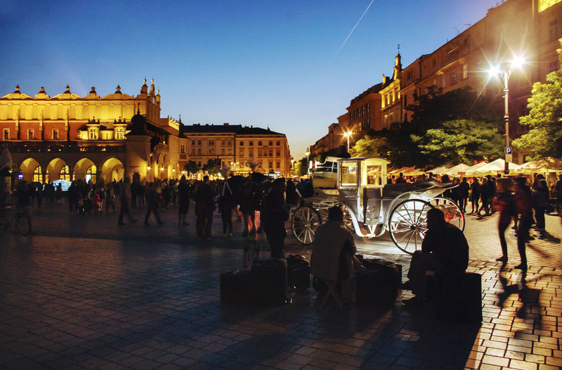 People at illuminated town square at night
