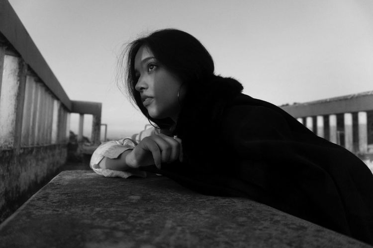 Side view of young woman leaning on retaining wall