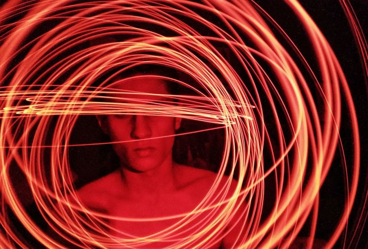 Close-Up Of Man With Light Painting At Home