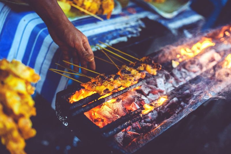 Cropped image of hand cooking satay on barbecue