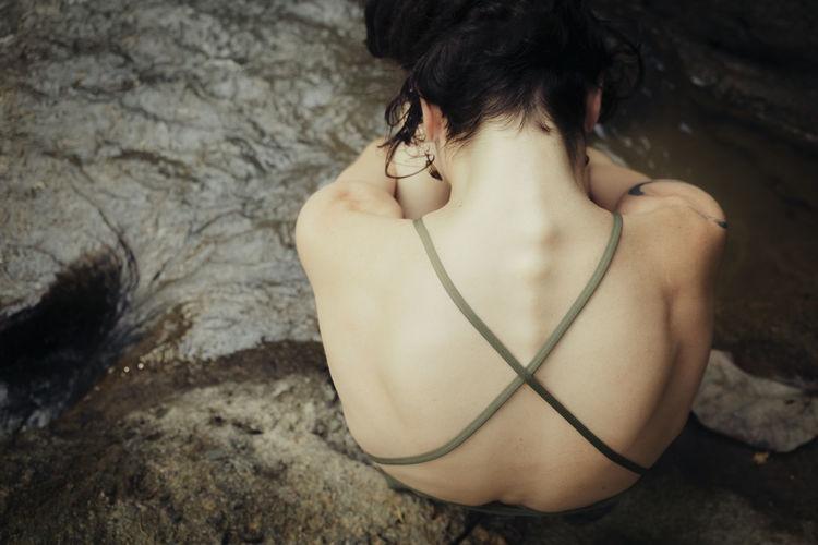 Rear view of sad woman wearing bikini while sitting on rock