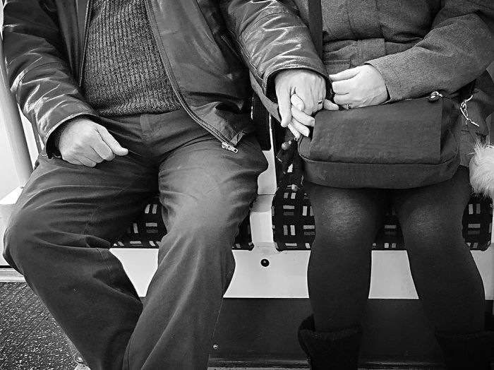 Midsection of couple holding hands while sitting in metro train
