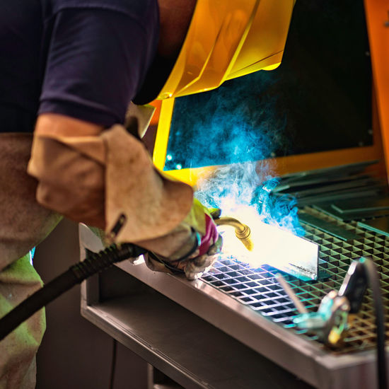 Close-up of worker welding metal at factory