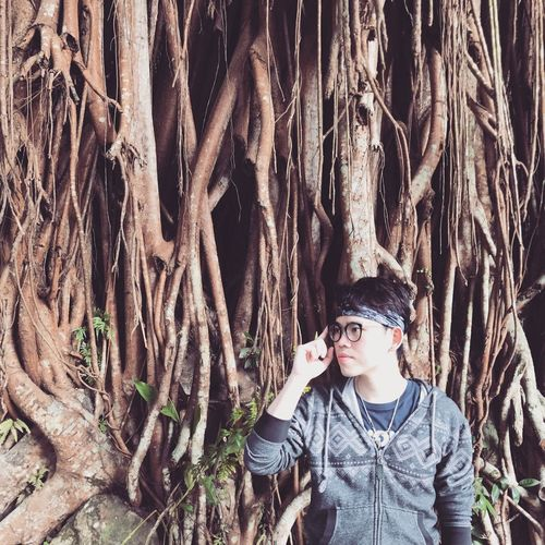 Handsome man standing against banyan tree