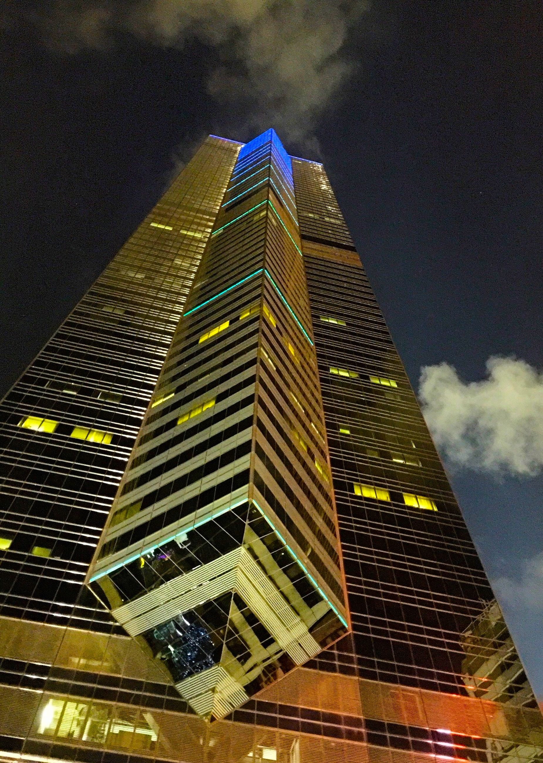 low angle view, architecture, built structure, building exterior, tall - high, tower, modern, illuminated, skyscraper, sky, city, night, office building, building, no people, outdoors, architectural feature, tall, famous place, pattern
