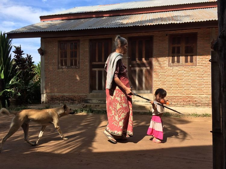 Young girl giving guidance to her blind grandmother Building Exterior Built Structure Guidance House Outdoors Real People Stray Dog Two People Women