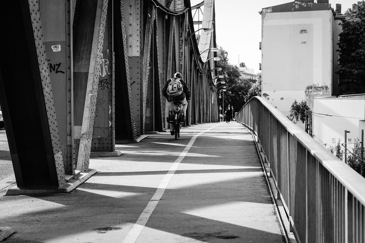 biker on the bridge Architecture Berlin Biker Bridge Brücke Built Structure City City Life Composition Diminishing Perspective Fahrradfahrer Geländer Gesundbrunnen Incidental People Leading Perspective Railing Sidewalk Street Streetphoto_bw The Way Forward Urbanphotography Walking