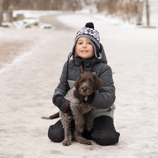 Friends Hiking Path Winter Boy Child Cute Day Dog Domestic Animals Full Length Griffon Happiness Looking At Camera Mammal One Animal One Person Outdoors Outdoors, Outside, Open-air, Air, Fresh, Fresh Air, Pets Puppy Sitting Smiling Trail Warm Clothing
