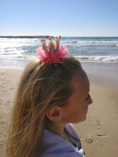 Close-up of girl wearing crown hair clip looking away at beach