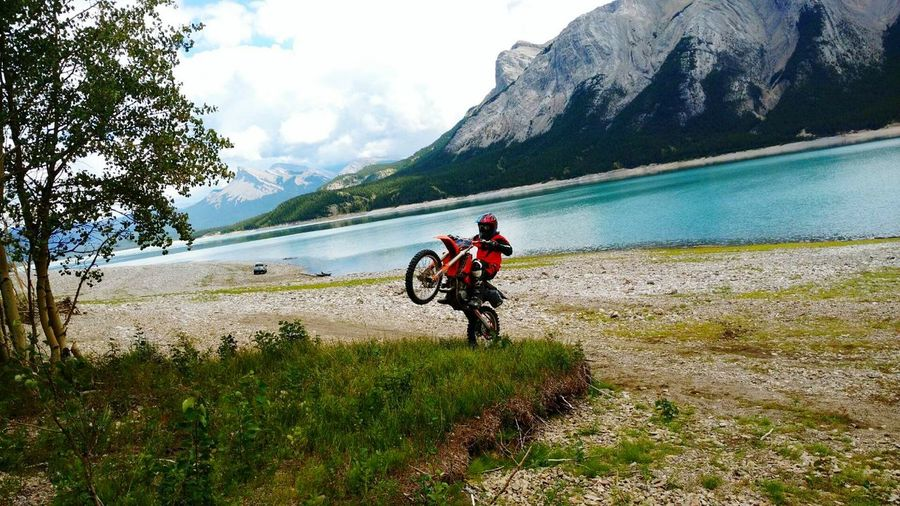 Man riding motorcycle at lakeshore against mountain