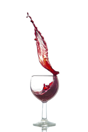 Close-up of red wine in glass against white background