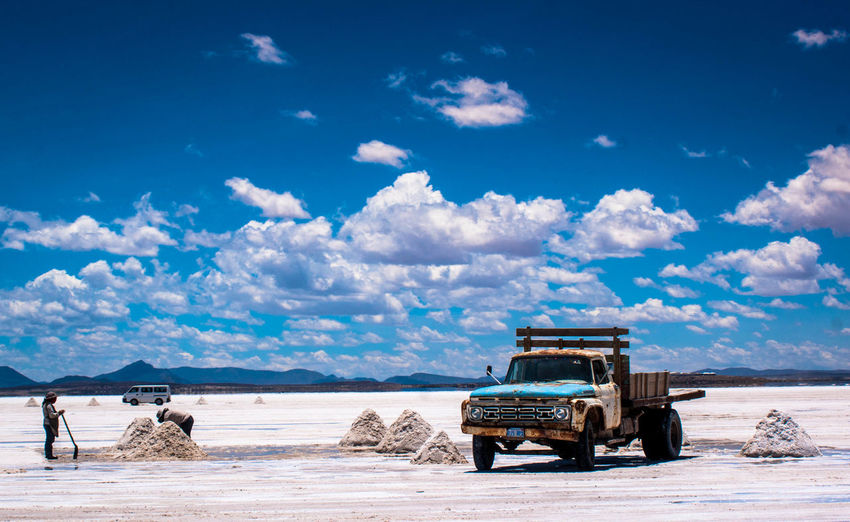 Truck on salt flat at salar de uyuni against sky