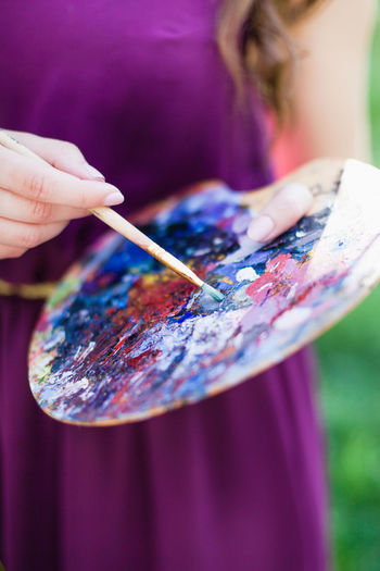 Midsection of woman holding palette and paintbrush