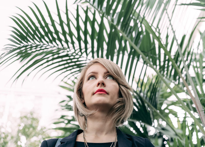Low Angle View Looking Up Women Portrait Of A Woman Green Eyes Beautiful Eyes Tree Young Women Portrait Headshot Beautiful Woman Palm Tree Front View Close-up Palm Leaf Thoughtful Thinking Caucasian Attractive Head And Shoulders Human Lips Ceremonial Make-up Red Lipstick Pretty Frond