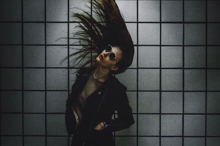 Woman tossing hair against wall