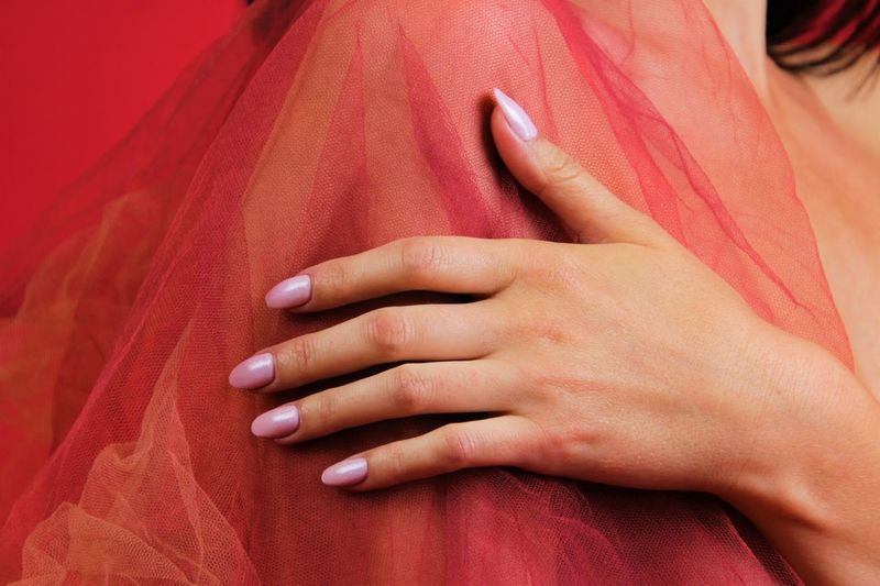 Close-up of woman touching red fabric
