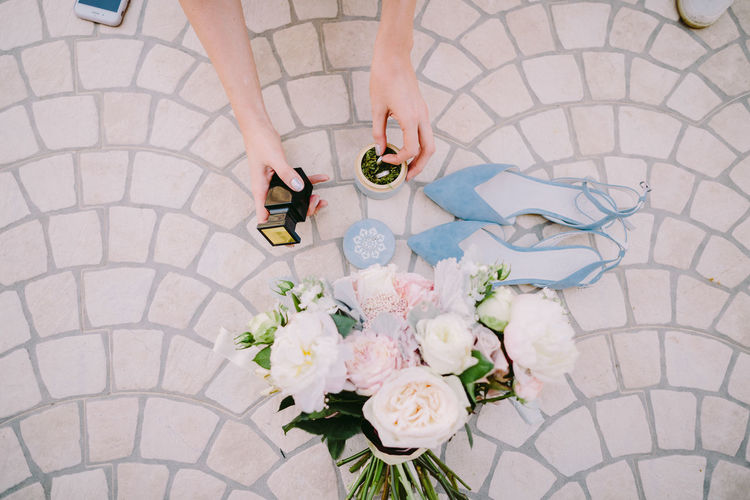 High Angle View Of Woman Holding Rings In Bottle By Bouquet On Footpath