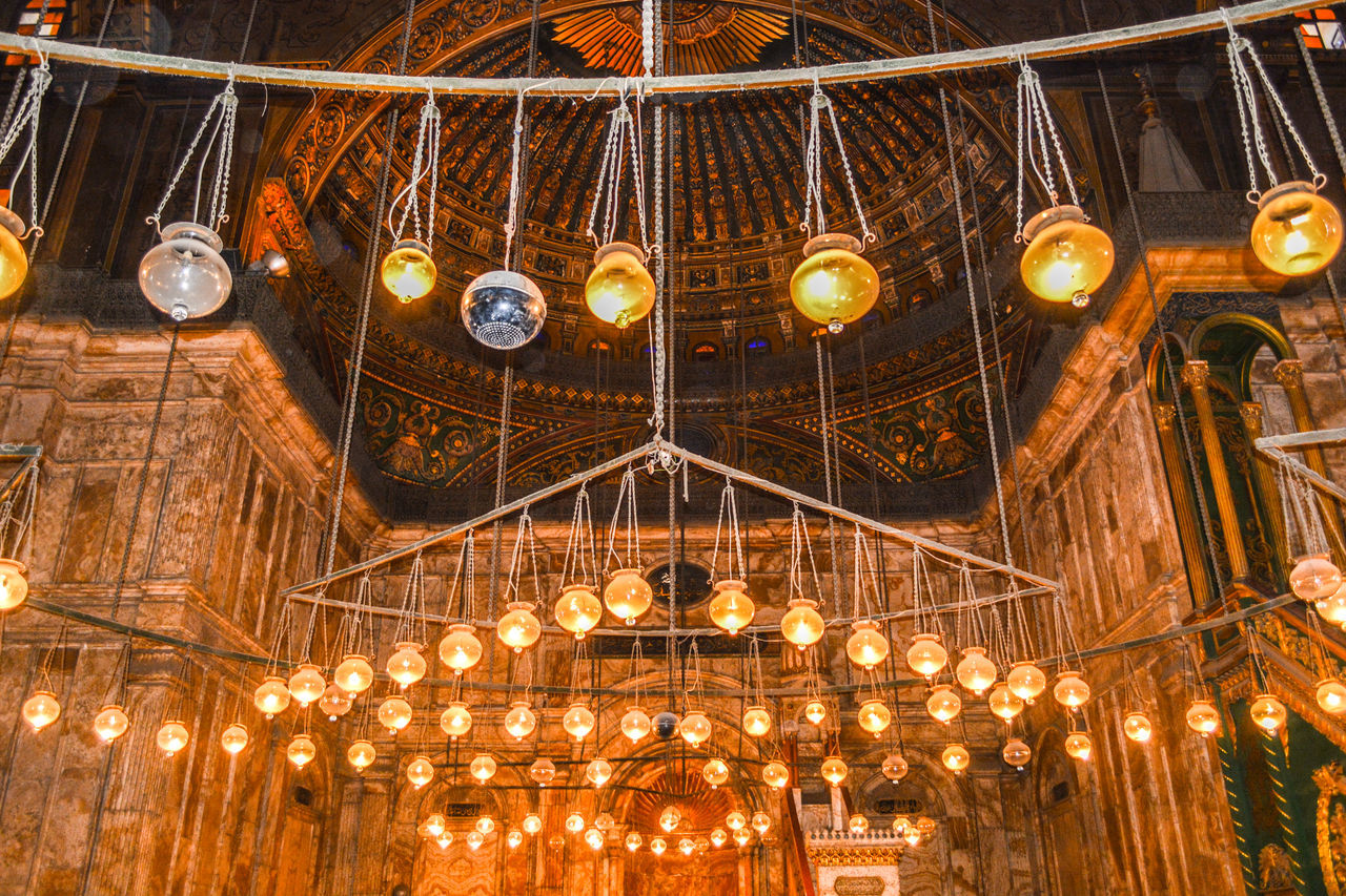 illuminated, lighting equipment, indoors, low angle view, light bulb, hanging, no people, night, gold colored, architecture