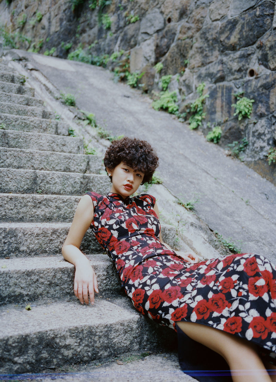 Low Angle Portrait Of Young Woman Sitting On Steps