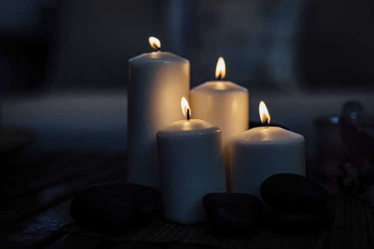 Close-up of burning light candles on table