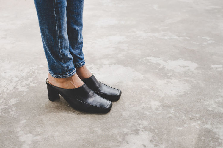 Black Color Body Part Casual Clothing Day Denim High Angle View Human Body Part Human Foot Human Leg Human Limb Jeans Leather Leisure Activity Lifestyles Low Section One Person Outdoors Real People Shoe Standing Women
