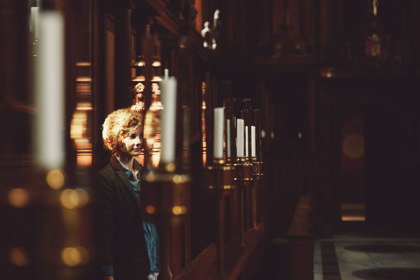 Architectural Column Blonde Candles Curly Hair Dark Depth Of Field Focus On Foreground Girl Illuminated Interior Lifestyles Light Lit Night Selective Focus Original Experiences Natural Light Portrait The Secret Spaces Connected By Travel