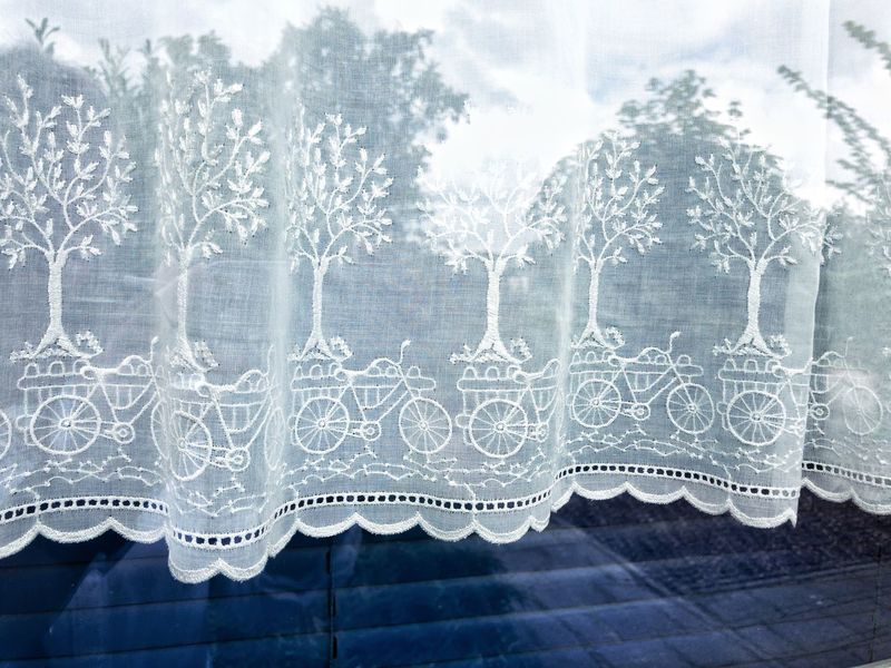 Opmeer, Netherland - August 12th 2017: Curtains with embroidered pattern of trees and bicycles No People Curtains Bicycles Pattern Trees Fragile Texture Window White Lace Textile