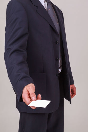 Midsection of businessman holding paper against white background