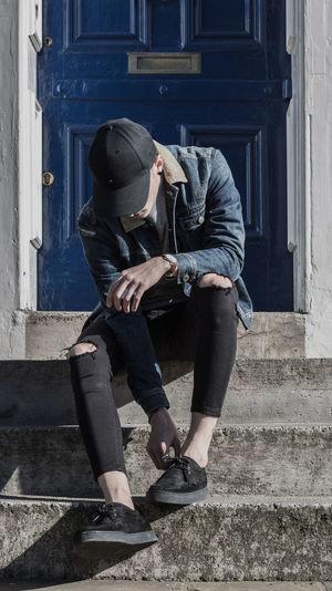 Man adjusting shoe on steps against door