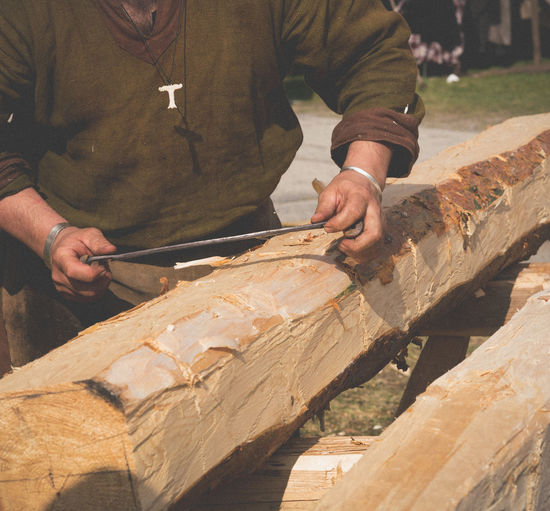 Midsection of carpenter cutting wood