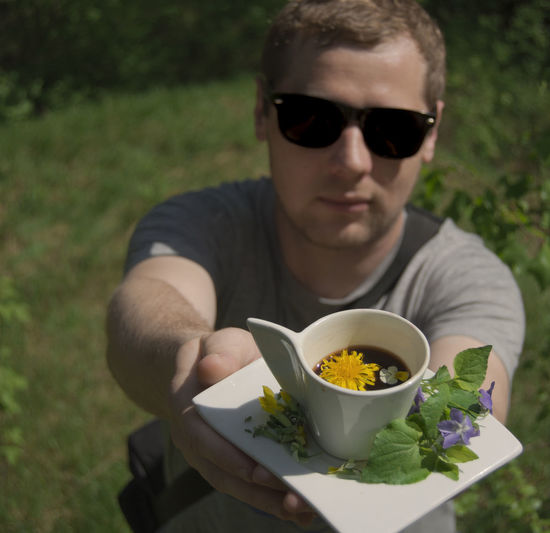 Coffee Casual Clothing Ceramics Coffee And Flowers Coffee Cup Cup Of Coffee Fashion Flowers Focus On Foreground Food And Drink Front View Glasses Holding In Hands Leisure Activity Lifestyles Nature One Person Outdoors Plant Portrait Real People Sunglasses Young Adult Young Men