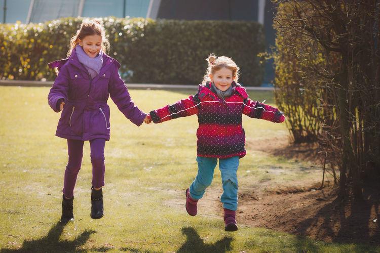 Full length of happy girls running on field