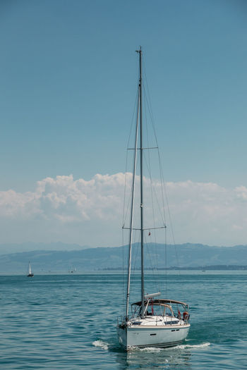 Nice little sailboat on a lake near the coast Nautical Vessel Sky Transportation Sea Water Mode Of Transportation Sailboat Pole Mast Sailing Cloud - Sky Nature Day Beauty In Nature Scenics - Nature Waterfront Travel No People Sailing Ship Outdoors Yacht Luxury