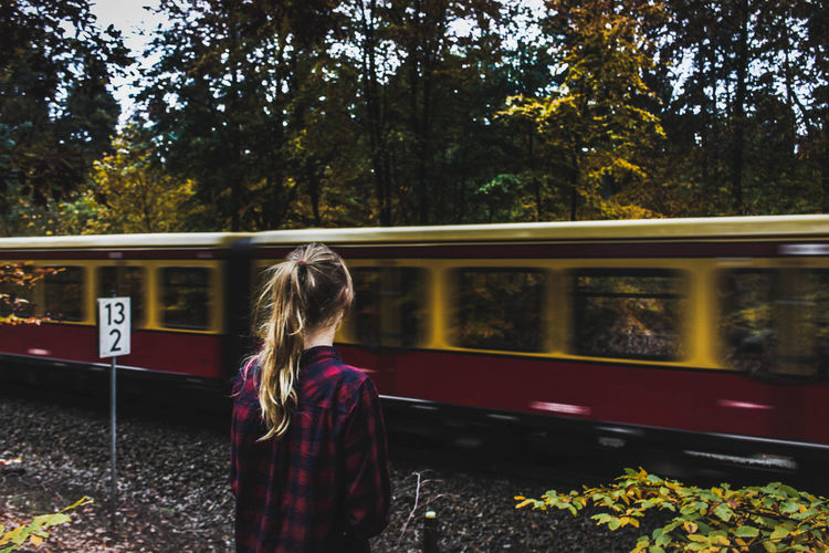 Woman standing by train against trees