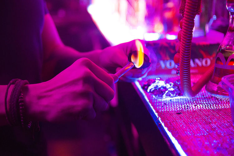 Midsection of man burning coal by hookah in illuminated nightclub